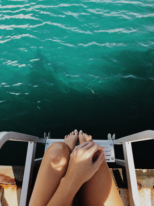 Image of woman's feet on boat ladder over ocean